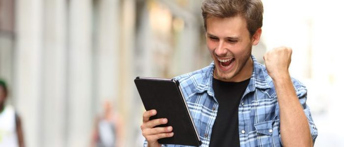 Euphoric winner man with a tablet