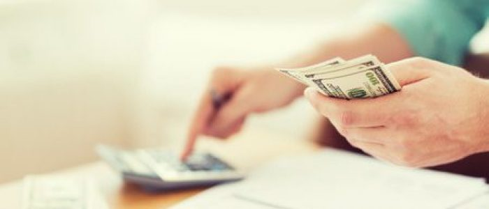 36972431 - close up of man with calculator counting money and making notes at home